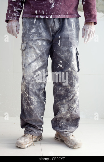 hands and white dirty trousers detail of plastering painter man - Stock Image