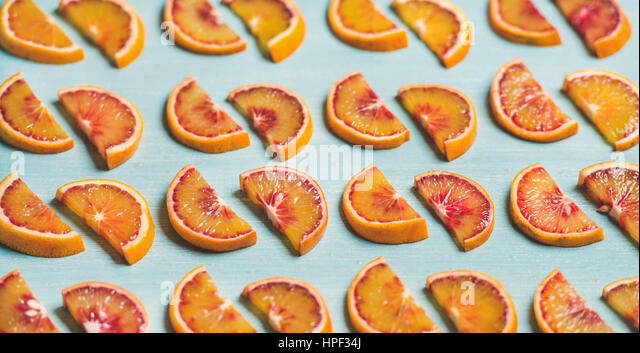 Natural fruit pattern concept. Fresh juicy blood orange slices placed in rows over light blue painted table background, - Stock Image