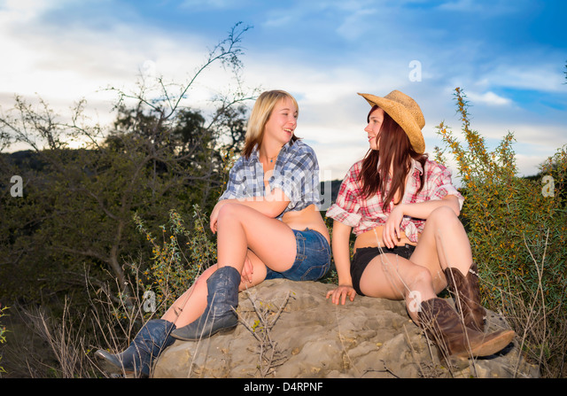 Friends - Two female teenagers in country girl attire sitting on a rock, Females 19 Caucasion, Texas, USA - Stock Image