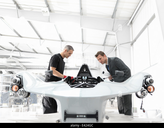 Engineer and automotive designer inspecting part-built supercar in car factory - Stock-Bilder