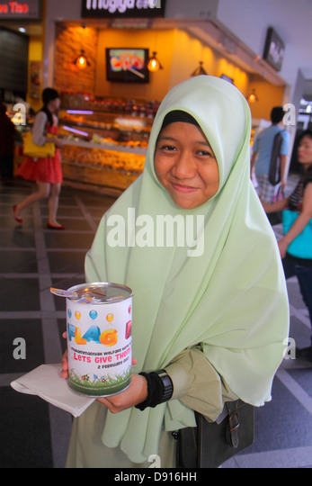 Singapore Kallang Road Asian teen girl Muslim collecting donations charity welfare home hijab - Stock Image