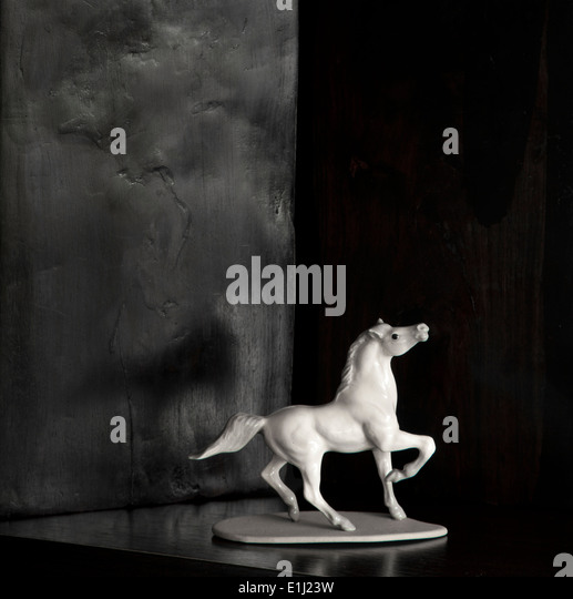 Horse figure of white porcelain in front of black background - Stock Image