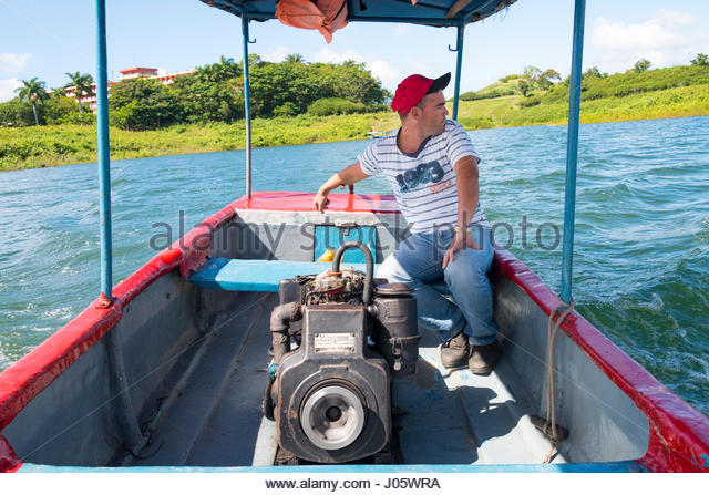 Cuban self employed man giving tours in the Hanabanilla natural reserve in private motor boat - Stock-Bilder
