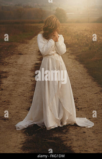 Lone woman with vintage bride dress in countryside . Purity and innocence - Stock Image