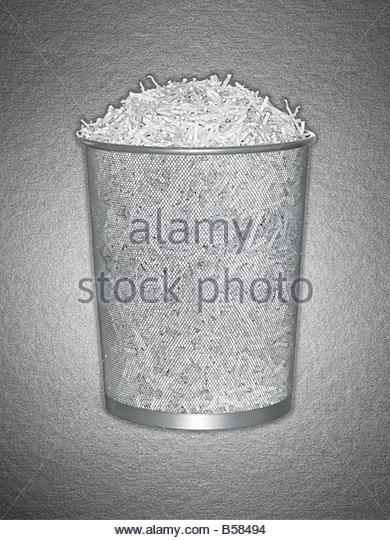 Wastebasket full of shredded paper - Stock Image