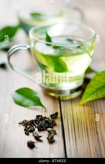 closeup of dry green tea, and a cup with fresh green tea. in the background, out of focus cup with fresh tea - Stock Image
