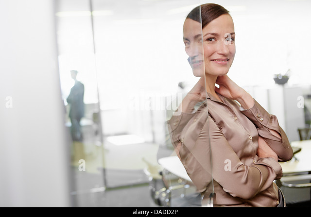 Woman wearing business attire standing in door frame of office - Stock Image
