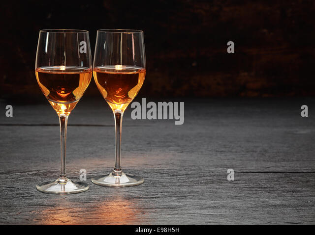 Pair of half-full half-empty wine glasses on stone surface - Stock Image