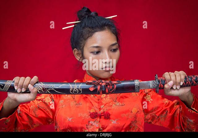 Asian woman holding a sword - Stock-Bilder