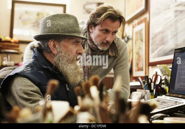 Senior and mid adult man using laptop in antique shop - Stock-Bilder