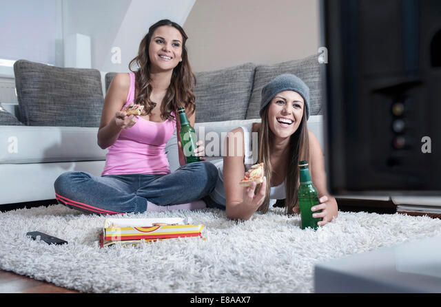 Two female friends side by side on carpet at home watching television - Stock Image