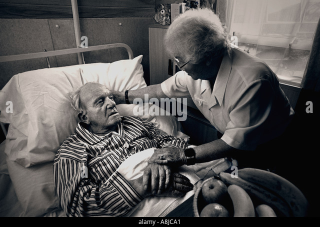 Visiting carer wife companion comforts elderly gentleman in his care home bed Black and White toned treatment - Stock-Bilder