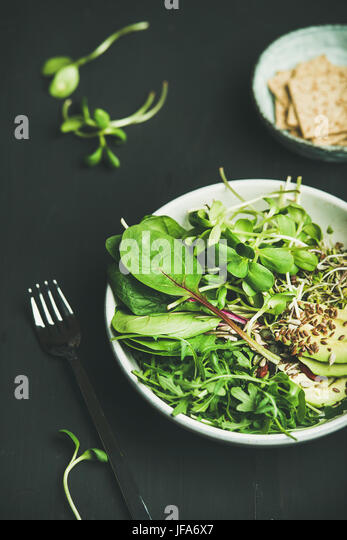 Breakfast with spinach, arugula, avocado, seeds and sprouts in bowl - Stock Image