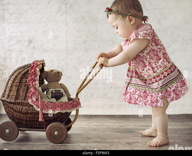 Little cute girl playing the toy carriage - Stock Image