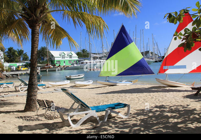Wind surfing boards sitting on a hotel beach near Falmouth Harbour Marina in Antigua Barbuda. - Stock Image