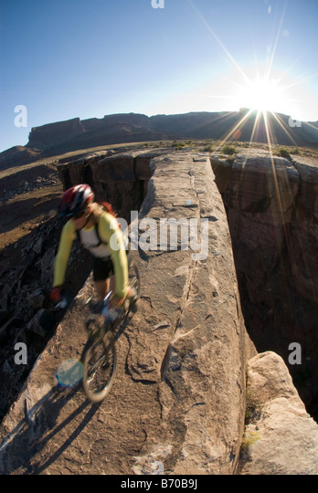 Mountain biker crossing sandstone bridge, Canyonlands, Utah. - Stock Image