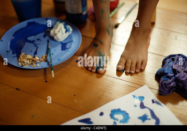 Young girl makes a mess painting in her room. - Stock Image