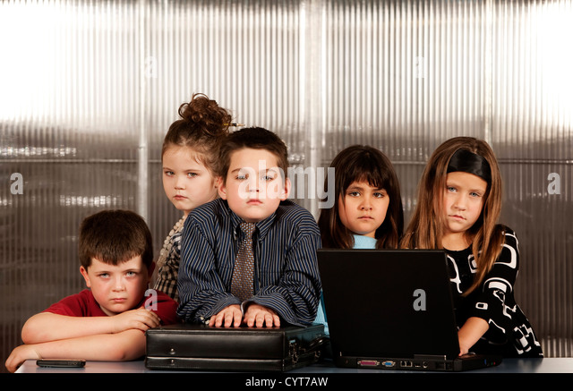 Kids posing as a professional business team - Stock Image
