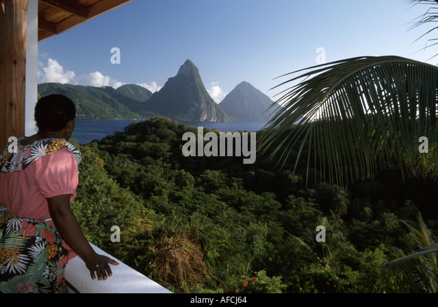 West Indies St. Lucia Anse Chastanet Resort guest room view balcony Les Pitons mountains Black female attendant - Stock Image