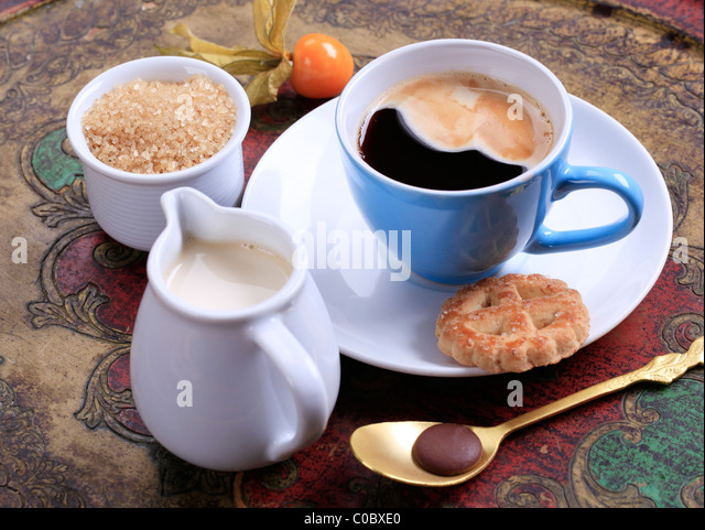 Cup of coffee, jug of cream and bowl of brown sugar - Stock Image