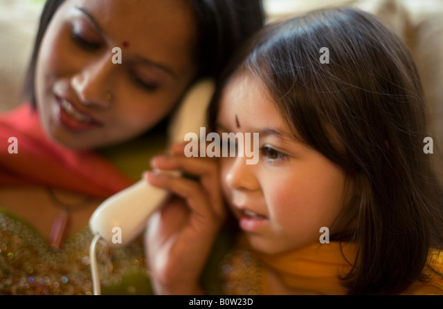 Pakistani mother and mixed race daughter in traditional dress telephone home - Stock-Bilder