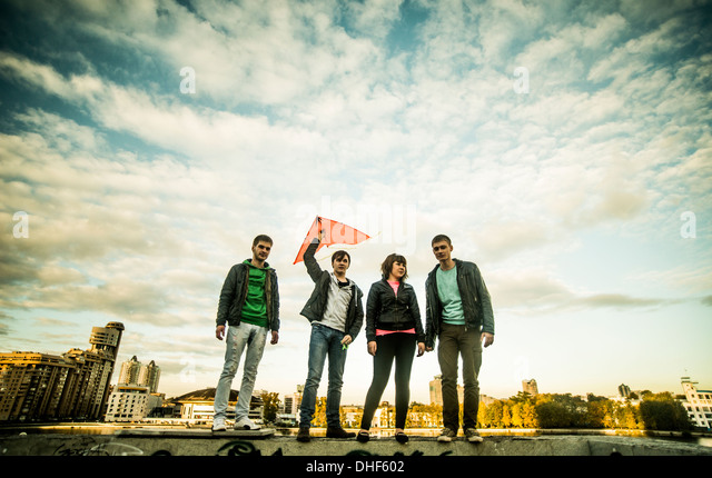 Four friends with one man holding kite, Russia - Stock Image