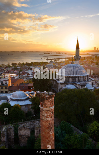 Setting sun behind the Sokollu Mehmet Pasha mosque minaret and historic Dervish ruins on the Marmara Sea Istanbul - Stock Image