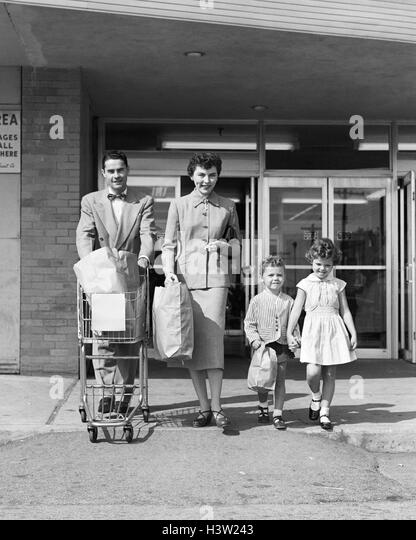 1950s FAMILY OF FOUR WALKING OUT OF GROCERY STORE FATHER PUSHING SHOPPING CART MOTHER AND SON CARRYING BAGS - Stock Image