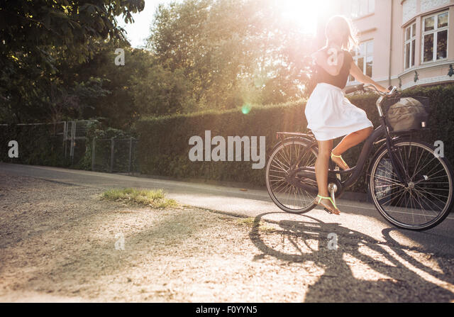Outdoor shot of a young woman cycling on street. Female riding bicycle with sun flare. - Stock Image