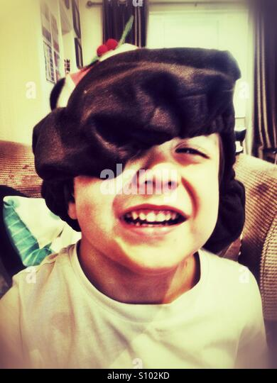 A happy young boy wearing a festive hat. - Stock Image