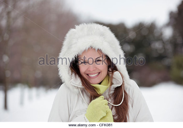 A young woman standing in the snow, trying to keep warm - Stock Image