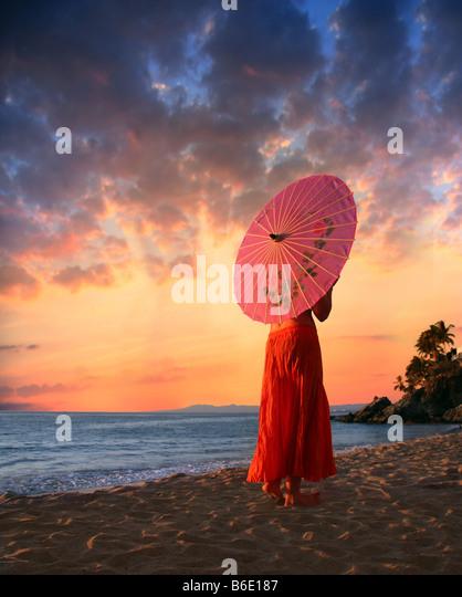 A woman in orange skirt walking on a beach - Stock Image