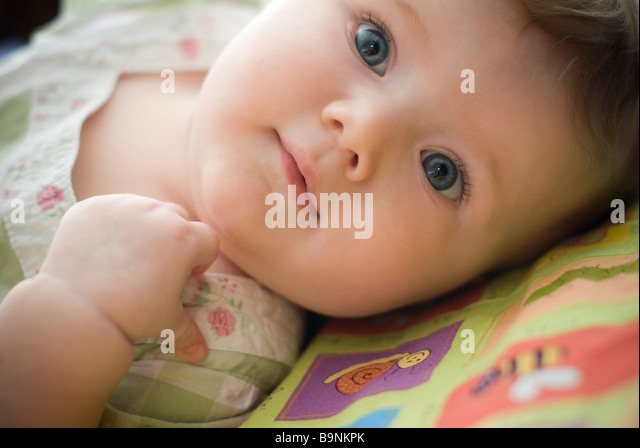 Baby girl lying down - Stock Image