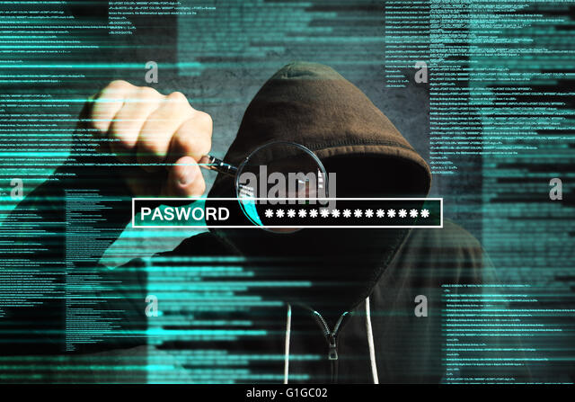 Hooded computer hacker with magnifying glass stealing internet password, online security concept. - Stock Image