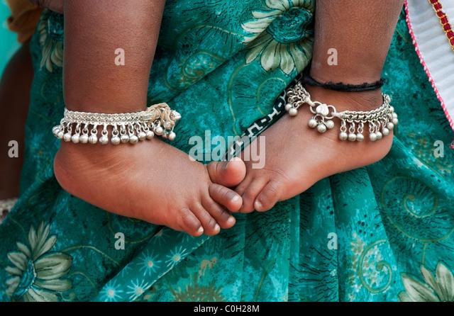 Indian babies bare feet against mothers green floral sari. Andhra Pradesh, India - Stock Image