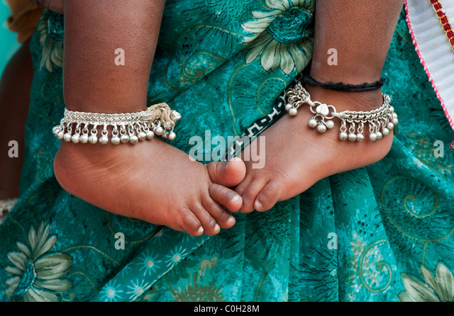 Indian babies bare feet against mothers green floral sari - Stock Image