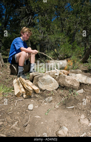 A young boy toasting marshmallow by a camp fire - Stock-Bilder