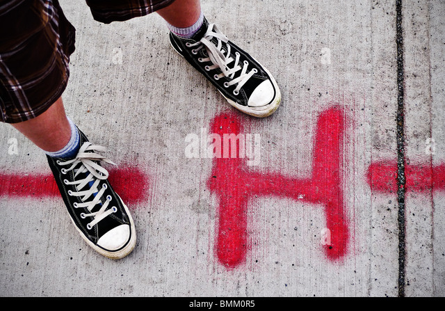 Urban youth with Converse high-tops standing beside spray painted H on sidewalk. - Stock Image