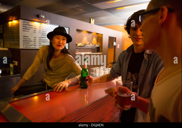 Three people sitting at bar with alcoholic drinks - Stock Image