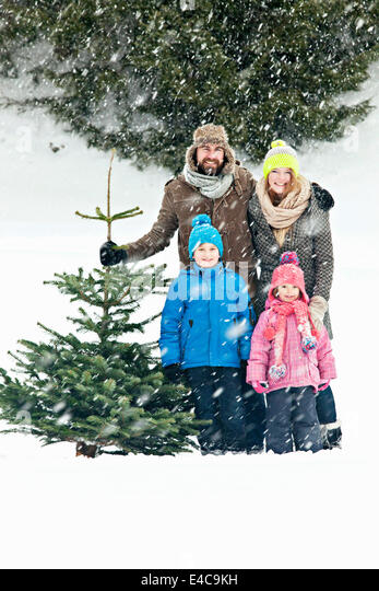 Family with two children stands with Christmas tree in snow-covered landscape, Bavaria, Germany - Stock Image
