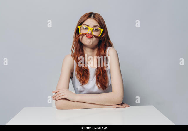 Caucasian woman sitting at table making a mustache with hair - Stock-Bilder