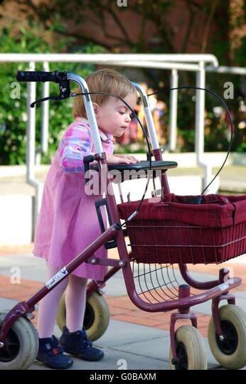 Child plays with a Rollator - Stock-Bilder