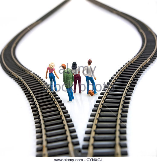 Model of four young people between tracks deciding which route to take - Stock Image