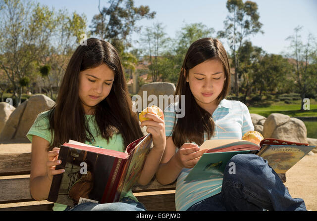California teens hanging out Vietnamese-Caucasian Hispanic Mexican girls 12-13 years old read reading books together - Stock-Bilder