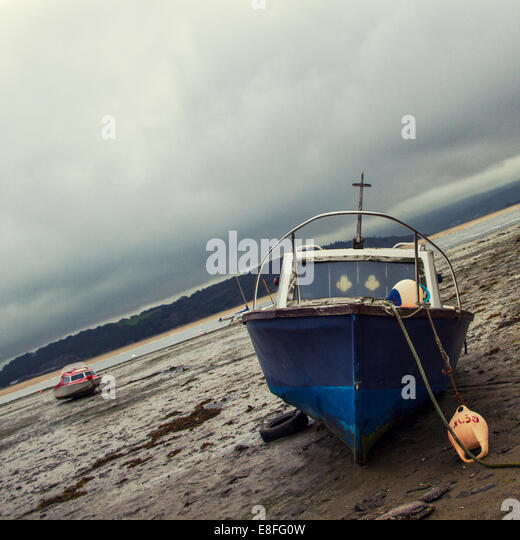 Fishing boat on beach at low tide - Stock Image