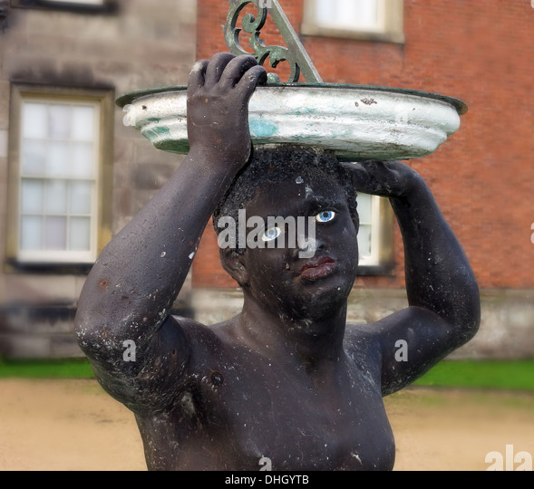Black African holding sundial at Dunham Massey Hall , near Altrincham Cheshire England , UK WA14 4SJ - Stock Image