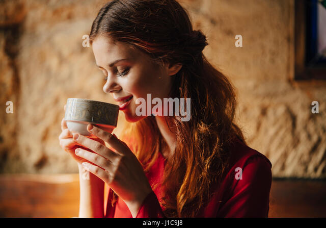 Caucasian woman sipping cup of tea - Stock Image