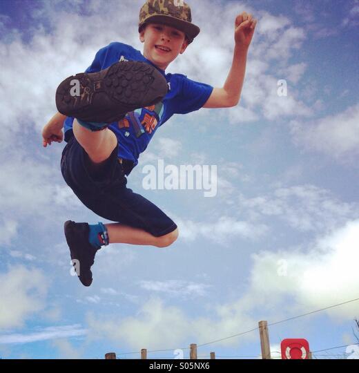 Boy jumping and having fun on beach - Stock Image
