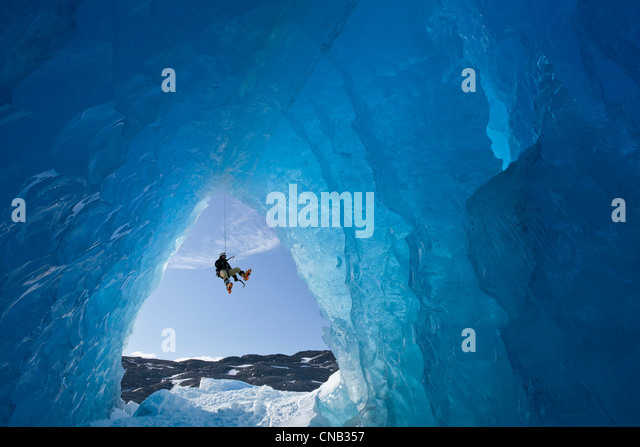 COMPOSITE: View from inside an ice cave of an iceberg as an ice climber rappels down, Mendenhall Glacier, Alaska - Stock Image