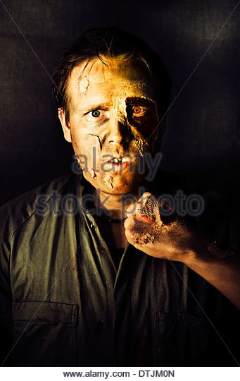 Dark Studio Portrait Of A Rotten And Mangled Zombie Raising A Clench Fist With A Deadly Intense Gaze During A Fight - Stock Image